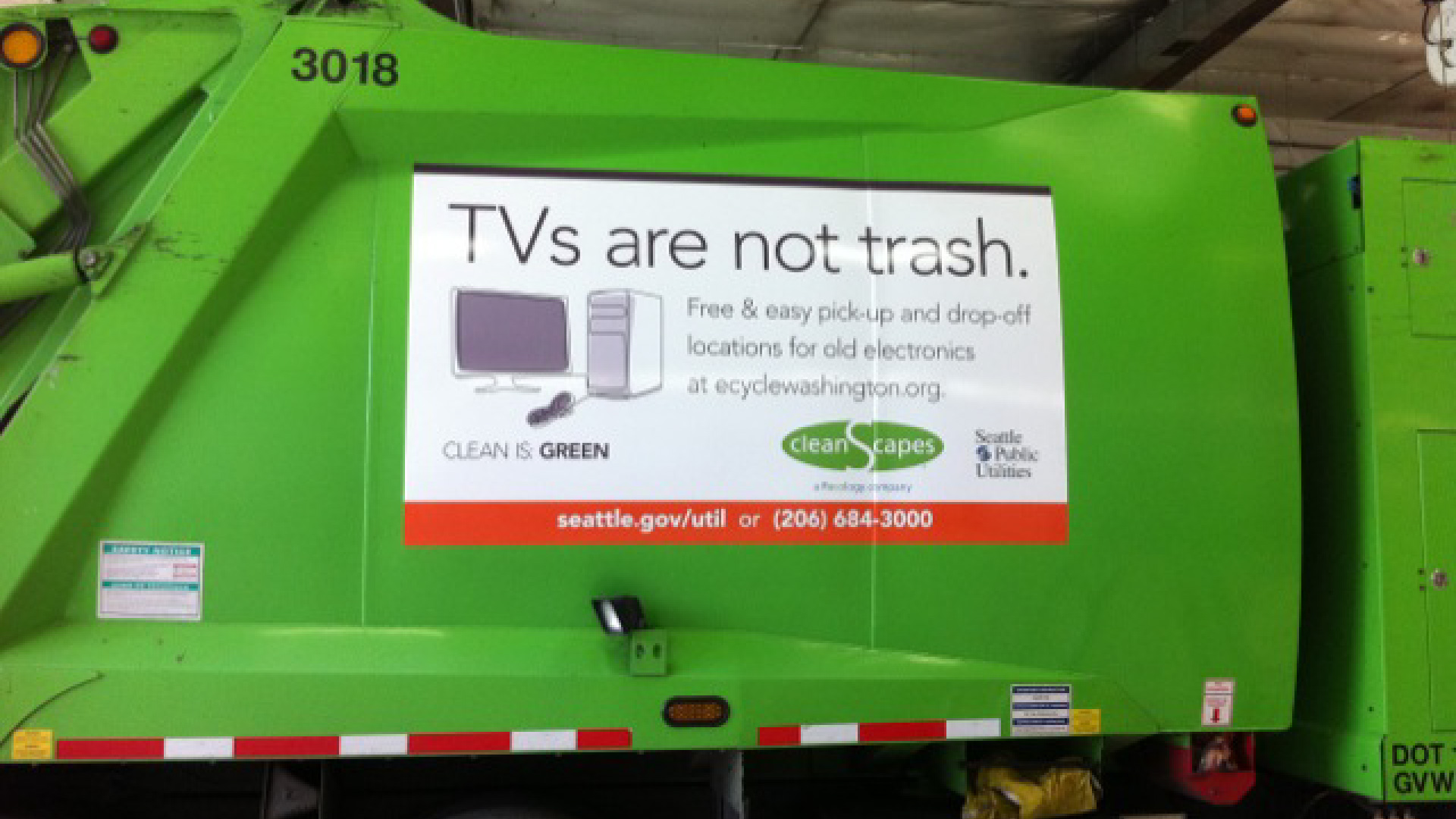 """Close up view of a bright green waste collection truck with a large graphic sign on the site with the headline """"TVs are not trash"""" and an illustration of electronics for recyling."""