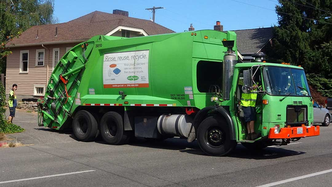 Large vinyl banner attached to side of waste disposal truck reading 'Rinse, Reuse, Recycle.' with illustration of plastic containers.