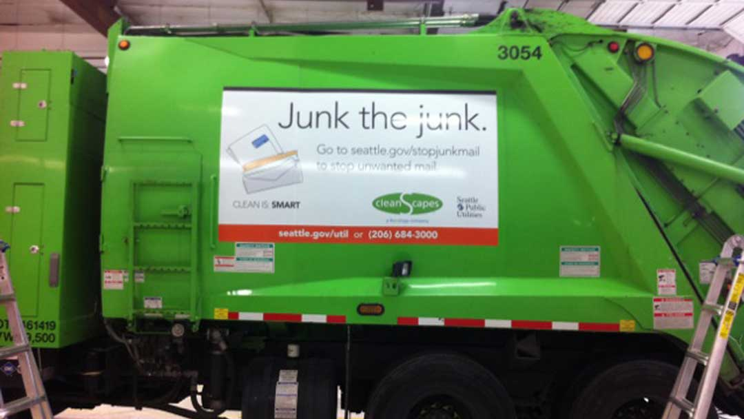 Large vinyl banner attached to side of waste disposal truck reading 'Junk the Junk.' with illustration of junk mail envelopes.