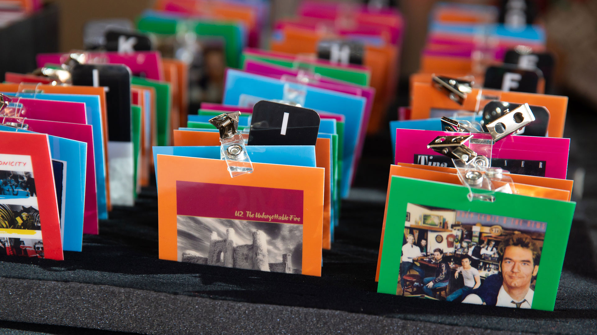 Reverse angle of name tags showing colorful back panels with 1980s album cover artwork