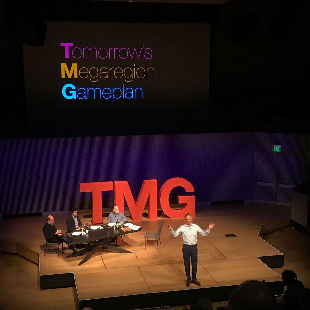 TMG Chairman standing center stage delivering closing remarks with large red TMG letters behind him, and a projected screen above which reads 'Tomorrows Megaregion Goals'.