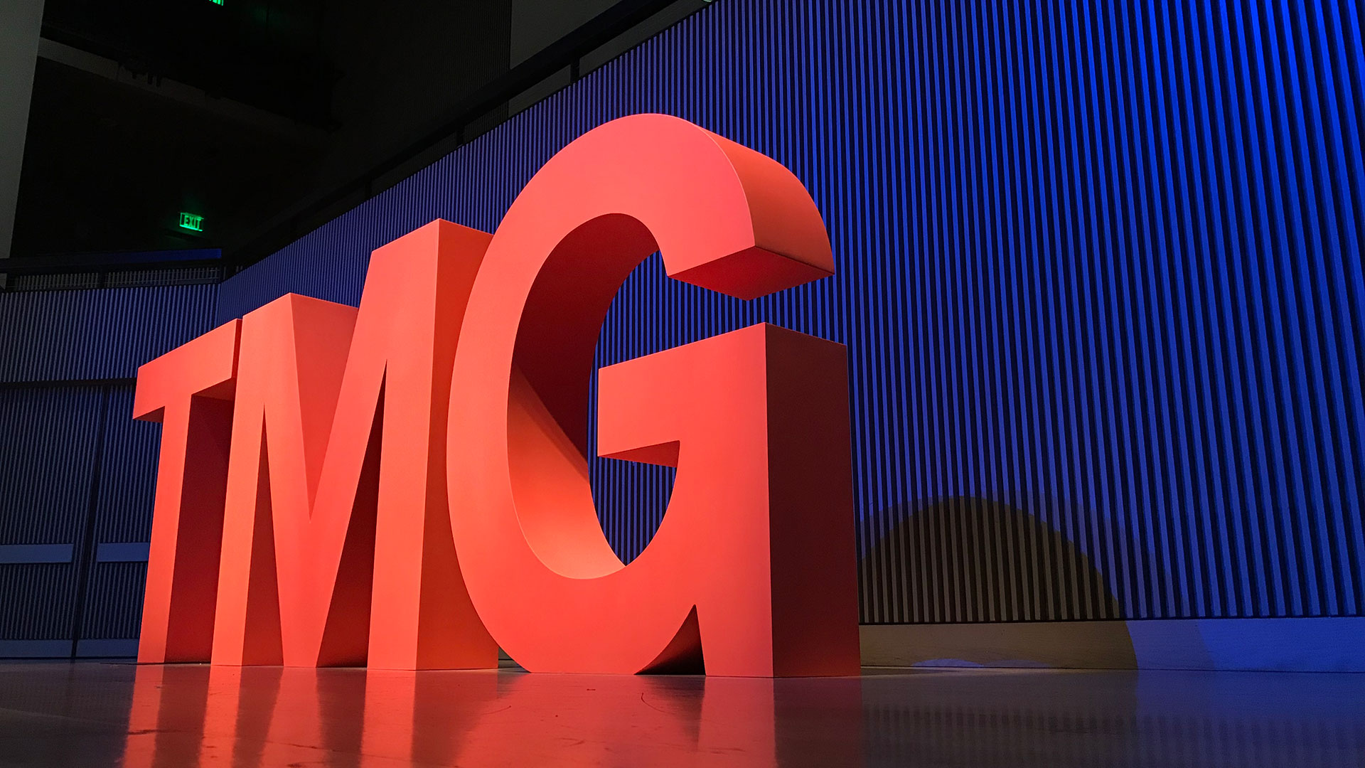 5 foot-tall wooden letters 'TMG' painted bright red on stage with blue light background.
